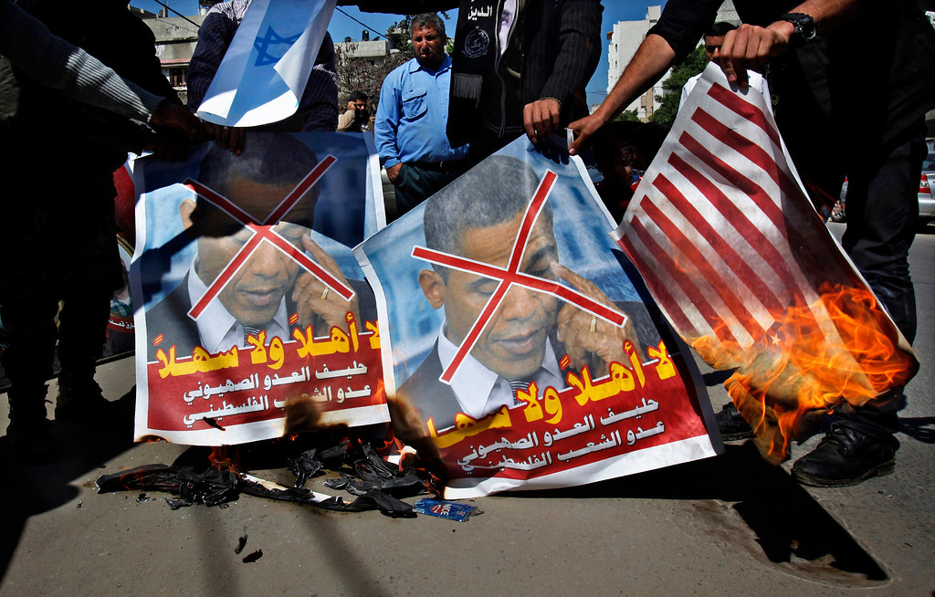 """. Palestinians burn posters of U.S. President Barack Obama and American flags during a protest against Obama\'s visit to the West Bank in Gaza City, Thursday, March 21, 2013. Arabic on posters read, \""""you are unwelcome, the ally of the Zionist enemy and the enemy of the Palestinian people.\"""" Obama is meeting Palestinian officials on the second day of his Mideast tour to emphasize the importance of reaching an Israeli-Palestinian peace deal. (AP Photo/Adel Hana)"""