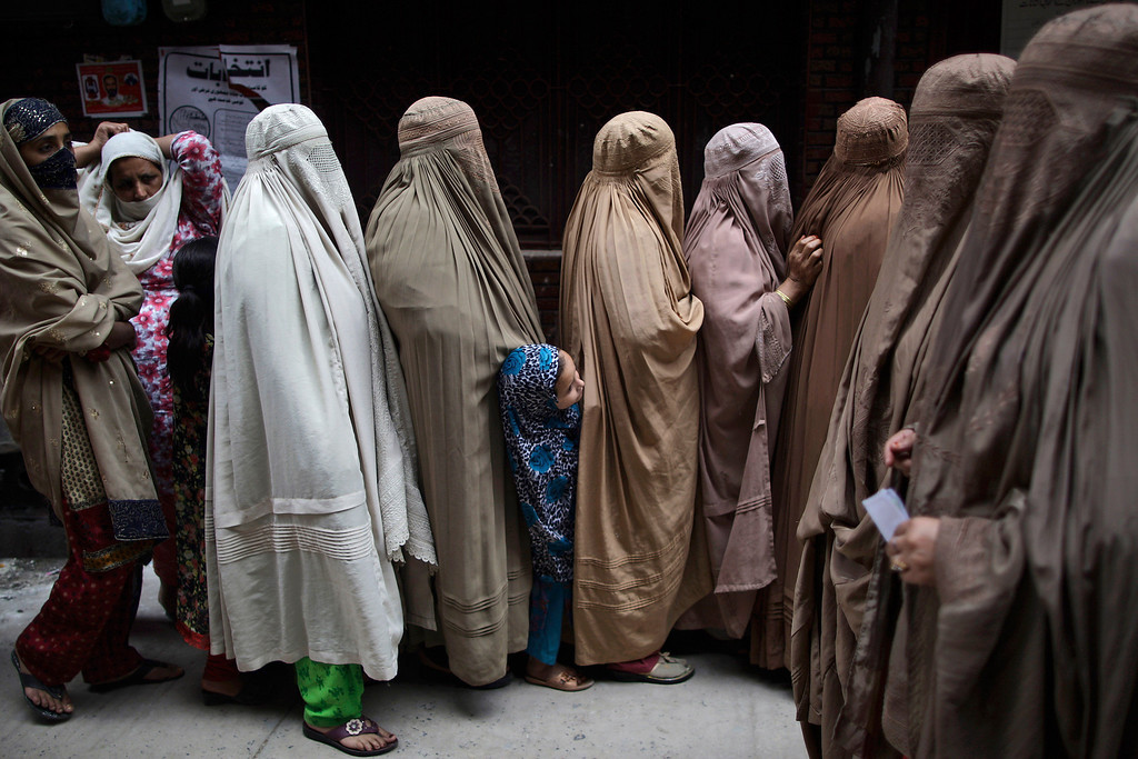 . A Pakistani girl stands between women waiting to enter a polling station to cast their ballots, in Rawalpindi, Pakistan, Saturday, May 11, 2013.  Defying the danger of militant attacks, Pakistanis streamed to the polls Saturday for a historic vote pitting a former cricket star against a two-time prime minister and an unpopular incumbent. But bombings that killed ten people and wounded dozens more underlined the risks many people took just casting their ballots.  (AP Photo/Muhammed Muheisen)