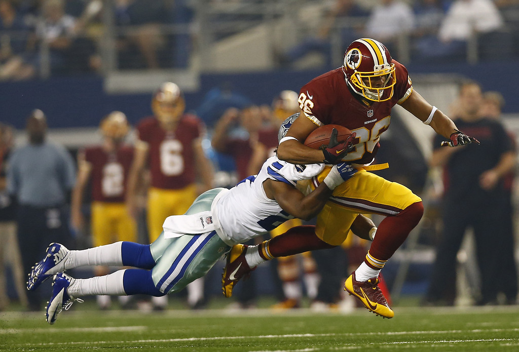 . Jordan Reed #86 of the Washington Redskins is hit by J.J. Wilcox #27 of the Dallas Cowboys during the first quarter at AT&T Stadium on October 13, 2013 in Arlington, Texas.  (Photo by Tom Pennington/Getty Images)