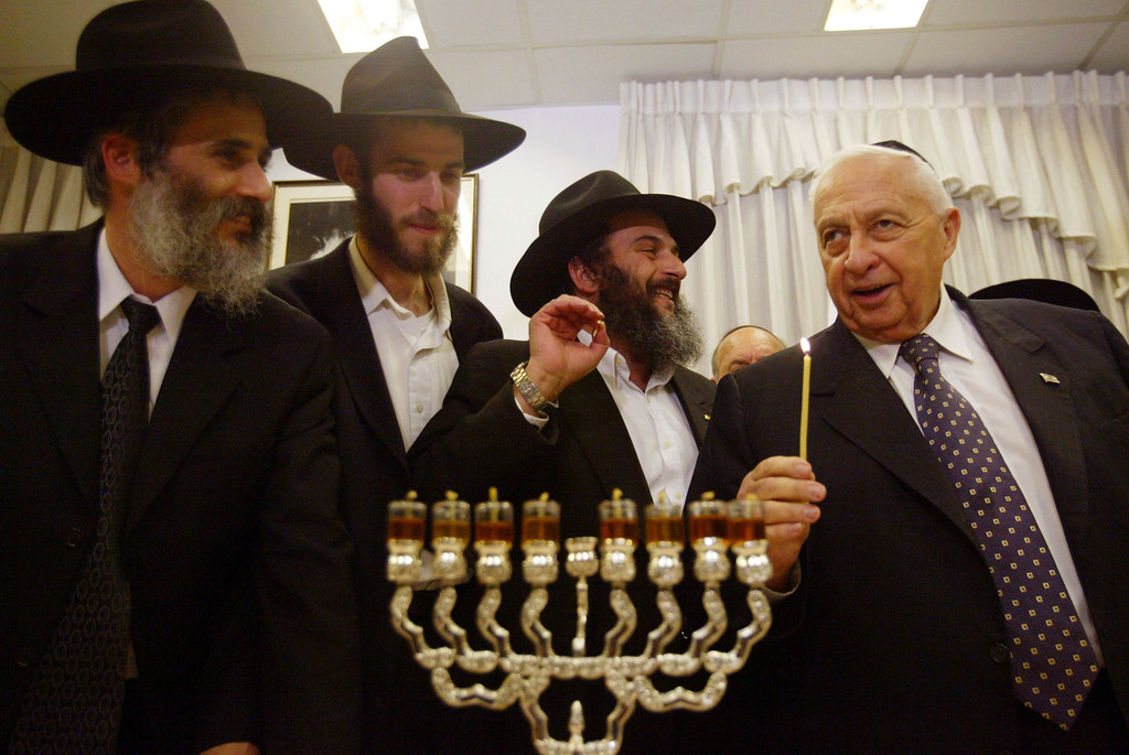". Israeli Prime Minister Ariel Sharon (R) prepares to light Hanukkah candles with Jewish rabbis at his office December 14, 2004 in Tel Aviv, Israel. Hanukkah, the ""Festival of Lights,\"" is eight days long and on each successive night an additional candle is lighted.  (Photo by Uriel Sinai/Getty Images)"