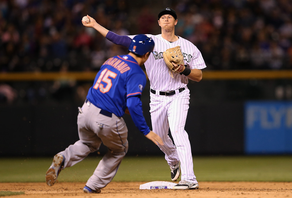 . DENVER, CO - MAY 02:  Second baseman DJ LeMahieu #9 of the Colorado Rockies turns a double play on Travis d\'Arnaud #15 of the New York Mets on a ground ball by Ruben Tejada #11 of the New York Mets in the sixth inning at Coors Field on May 2, 2014 in Denver, Colorado.  (Photo by Doug Pensinger/Getty Images)