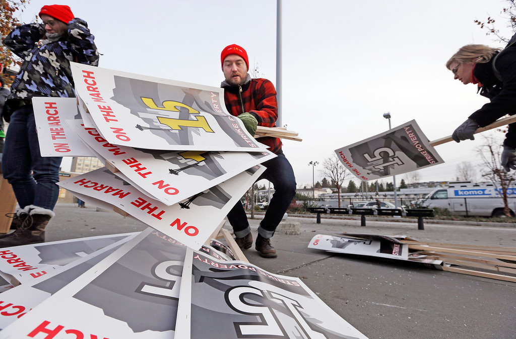 . Cary Davis drops a load of protest signs in preparation for a day-long march in support of fast-food workers Thursday, Dec. 5, 2013, in SeaTac, Wash. Demonstrators planned an eight-hour march Thursday, part of a nationwide-protest for higher wages. Workers, activists and community supporters met in in SeaTac and expected to continue to Seattle City hall, a 12-mile journey. (AP Photo/Elaine Thompson)