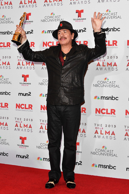 . PASADENA, CA - SEPTEMBER 27:  Honoree Carlos Santana (posing with the award for Outstanding Commitment to Cause and Community) attends the Winner\'s Walk during the 2013 NCLR ALMA Awards at Pasadena Civic Auditorium on September 27, 2013 in Pasadena, California.  (Photo by Alberto E. Rodriguez/Getty Images for NCLR)