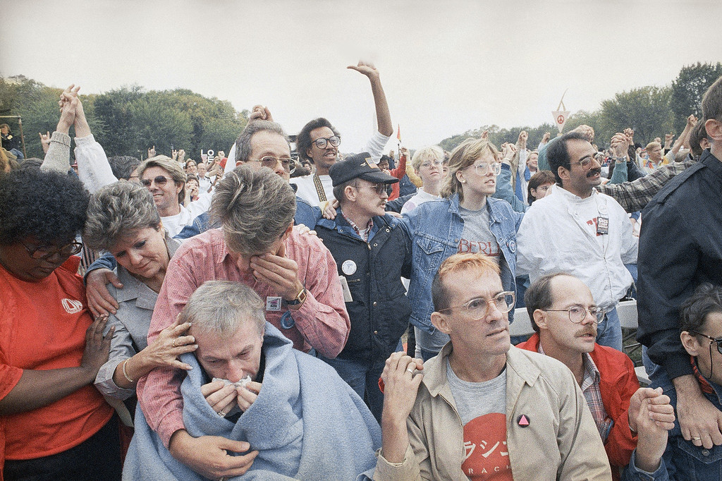 . An identified woman tries to comfort a wheelchair-bound Aids victim and his friend during the rally on the Mall for the participants of the Lesbian and Gay Rights March on Washington, Sunday, Oct. 11, 1987, Washington, D.C. Park police estimate some 200,000 people attended the rally. (AP Photo/Scott Stewart)