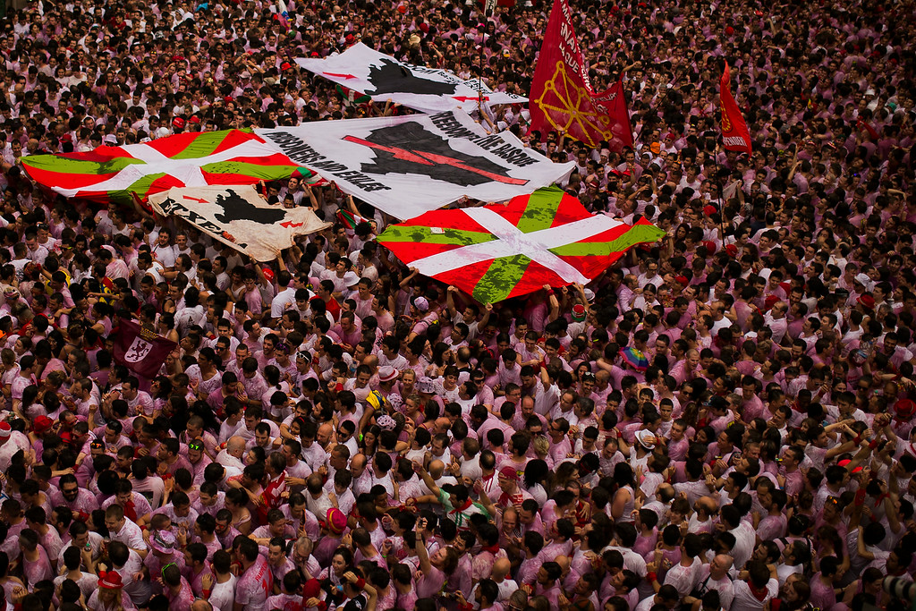 ". Revelers hold a Basque pro independence flag and a banner reading ""Freedom for the Basques, prisoners and exiles\"" after the launch of the \'Chupinazo\' rocket, to celebrate the official opening of the 2014 San Fermin fiestas, in Pamplona, Spain, Sunday, July 6, 2014. Revelers from around the world turned out here to kick off the festival with a messy party in the Pamplona town square, one day before the first of eight days of the running of the bulls glorified by Ernest Hemingway\'s 1926 novel \""The Sun Also Rises.\"" (AP Photo/Andres Kudacki)"