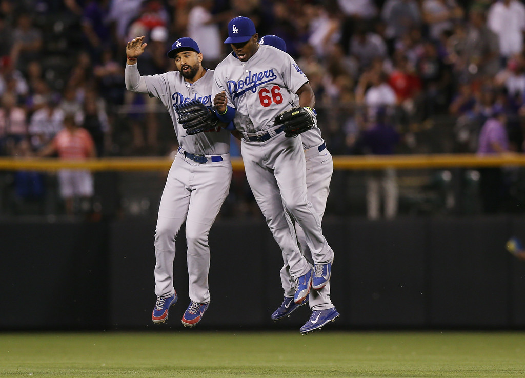 . Los Angeles Dodgers outfielders Matt Kemp, front left, and Yasiel Puig, front right, and Scott Van Slyke, back, celebrate after their 3-2 victory over the Colorado Rockies in a baseball game in Denver, Thursday, July 3, 2014. (AP Photo/David Zalubowski)