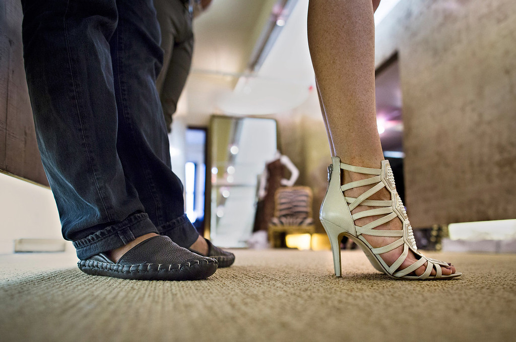 . Fashion designer Carmen Marc Valvo, left, stands with his model Taylor Foster as she tests outfits in a hallway that doubles as a runway at Valvo\'s New York studio. Valvo will show his Spring 2014 collection on Sept. 6 at Lincoln Center in New York. (AP Photo/John Minchillo)