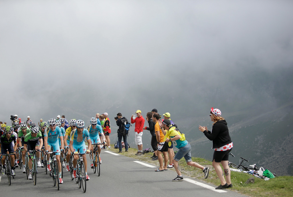 . The pack with Italy\'s Vincenzo Nibali, wearing the overall leader\'s yellow jersey, climbs Tourmalet pass in the mist during the eighteenth stage of the Tour de France cycling race over 145.5 kilometers (90.4 miles) with start in Pau and finish in Hautacam, Pyrenees region, France, Thursday, July 24, 2014. (AP Photo/Laurent Cipriani)