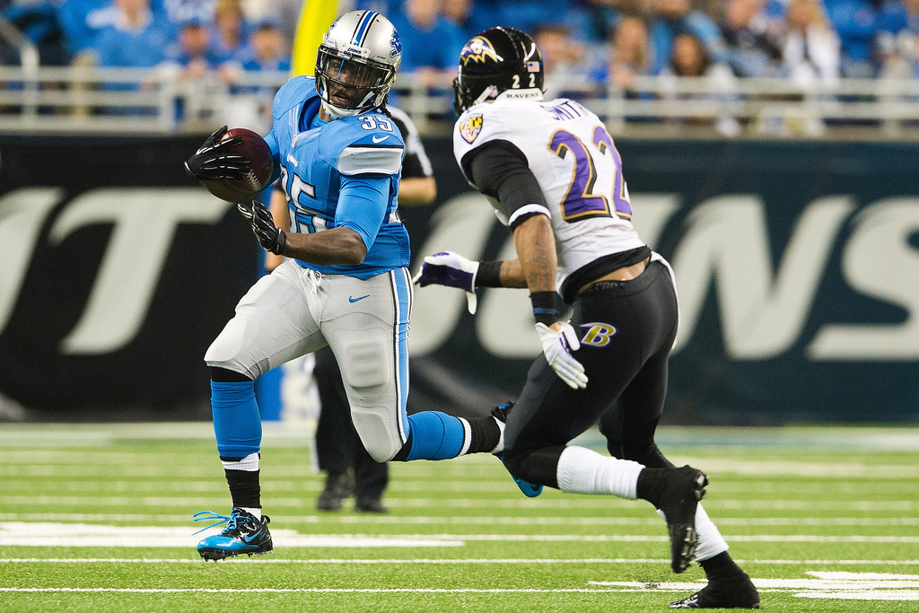 . Running back Joique Bell #35 of the Detroit Lions runs for a gain while under pressure from cornerback Jimmy Smith #22 of the Baltimore Ravens during the first half at Ford Field on December 16, 2013 in Detroit, Michigan. (Photo by Jason Miller/Getty Images)