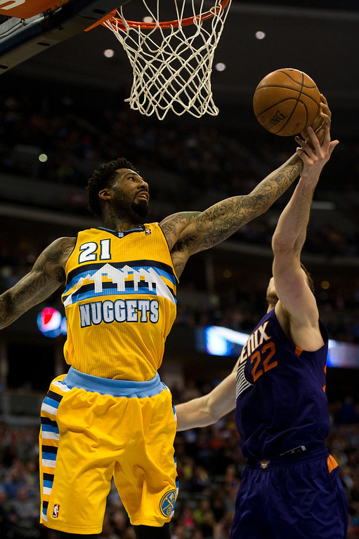 . DENVER, CO - DECEMBER 20: Wilson Chandler #21 of the Denver Nuggets reaches for a rebound against Miles Plumlee #22 of the Phoenix Suns at the Pepsi Center on December 20, 2013, in Denver, Colorado. The Suns won 103-99. (Photo by Daniel Petty/The Denver Post)