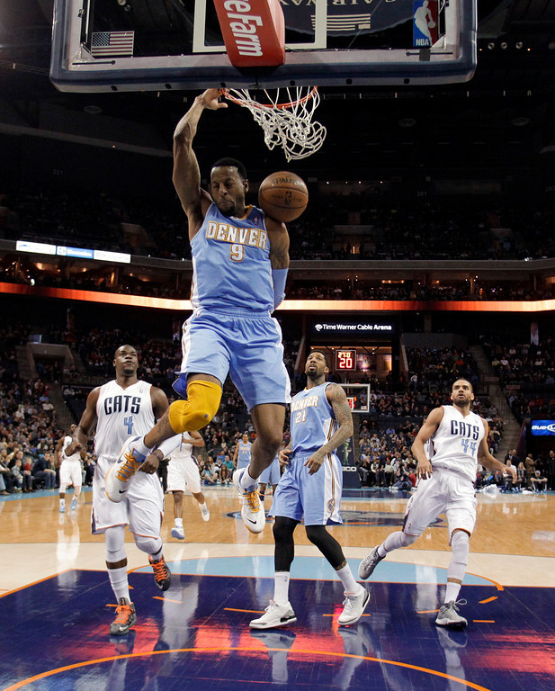 . Denver Nuggets\' Andre Iguodala (9) dunks as he gets in front of Charlotte Bobcats\' Jeff Adrien (4), Nuggets\' Wilson Chandler (21) and Bobcats\' Jeffery Taylor (44) during the first half of an NBA basketball game in Charlotte, N.C., Saturday, Feb. 23, 2013. (AP Photo/Bob Leverone)