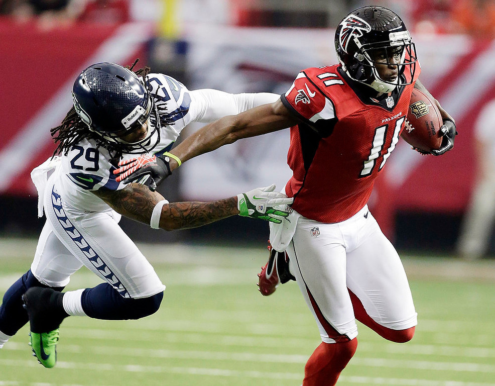 . Atlanta Falcons wide receiver Julio Jones (11) tries to get away from Seattle Seahawks\' Earl Thomas (29) during the first half of an NFC divisional playoff NFL football game Sunday, Jan. 13, 2013, in Atlanta. (AP Photo/Dave Martin)