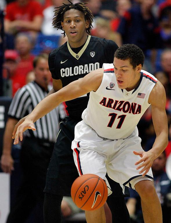 . Arizona\'s Aaron Gordon (11) loses control of the ball in front of Colorado\'s Xavier Johnson during the second half of an NCAA college basketball game Thursday, Jan. 23, 2014, in Tucson, Ariz. Arizona won 69-57. (AP Photo/John Miller)