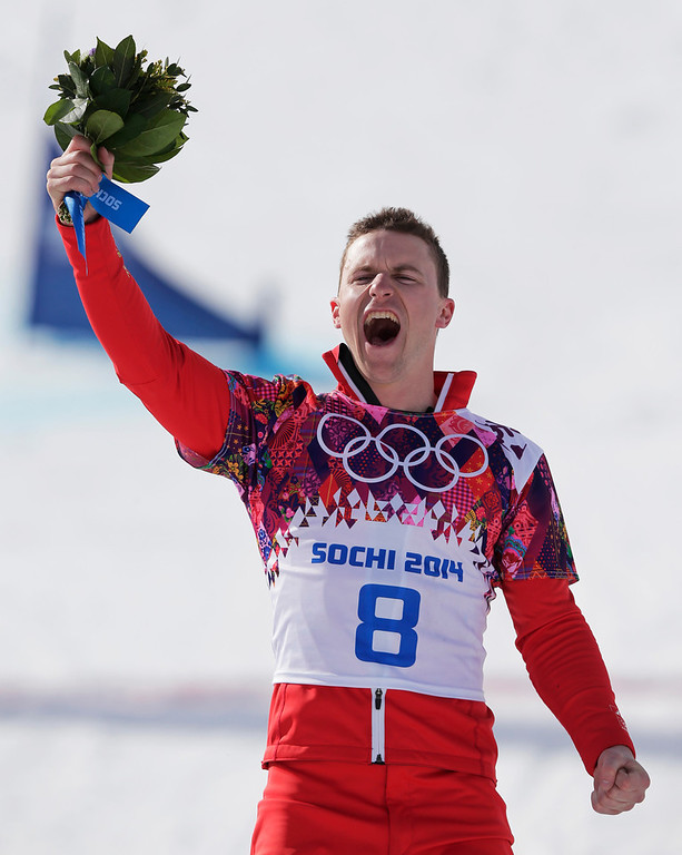 . Men\'s snowboard parallel giant slalom silver medalist Nevin Galmarini of Switzerland celebrates on the podium at the Rosa Khutor Extreme Park, at the 2014 Winter Olympics, Wednesday, Feb. 19, 2014, in Krasnaya Polyana, Russia. (AP Photo/Andy Wong)