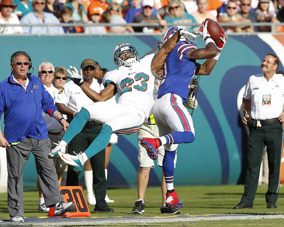 . T.J. Graham #11 of the Buffalo Bills catches the ball while being defended by Bryan McCann #23 of the Miami Dolphins on December 23, 2012 at Sun Life Stadium in Miami Gardens, Florida. The Dolphins defeated the Bills 24-10. (Photo by Joel Auerbach/Getty Images)