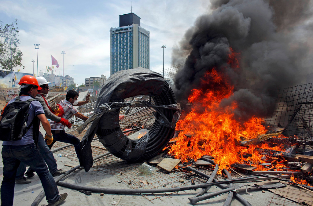 . Protesters push a cable wheel into a burning barricade during a protest at Taksim Square in Istanbul June 11, 2013.   REUTERS/Murad Sezer