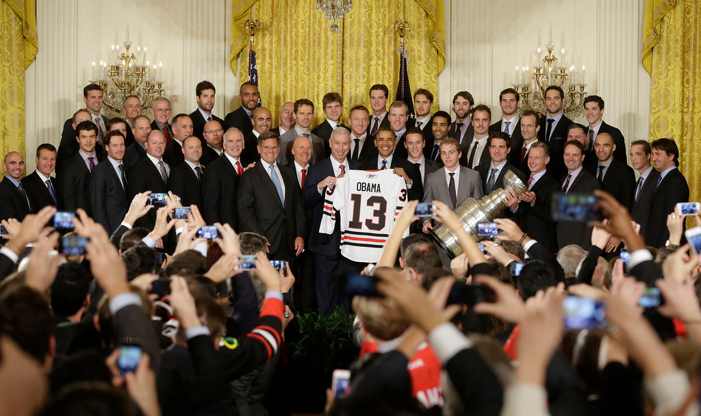 . President Barack Obama, center, holds up a Chicago Blackhawks hockey jersey with members of the team during a ceremony in the East Room of the White House in Washington, Monday, Nov. 4, 2013, where he honored the NHL 2013 Stanley Cup champion Chicago Blackhawks hockey team. (AP Photo/Pablo Martinez Monsivais)