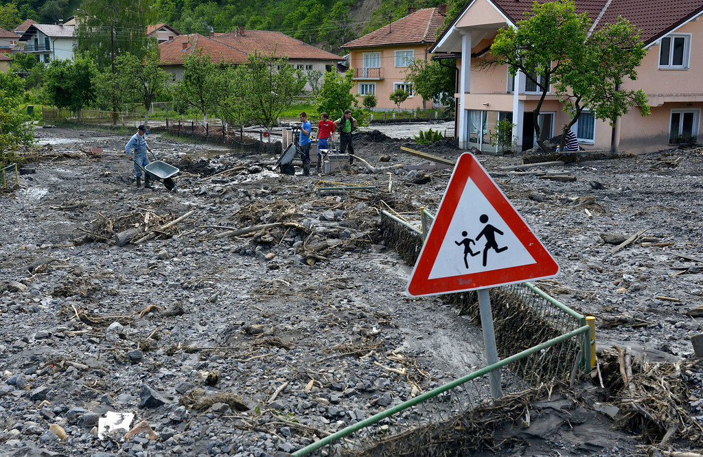 . Residents clean streets of mud and rubble after a landslide at the village of Topcic Polje, near the Bosnian town of Zenica, 90 kilometers north of Sarajevo, Bosnia-Herzegovina, Tuesday May 20, 2014. (AP Photo/Sulejman Omerbasic)