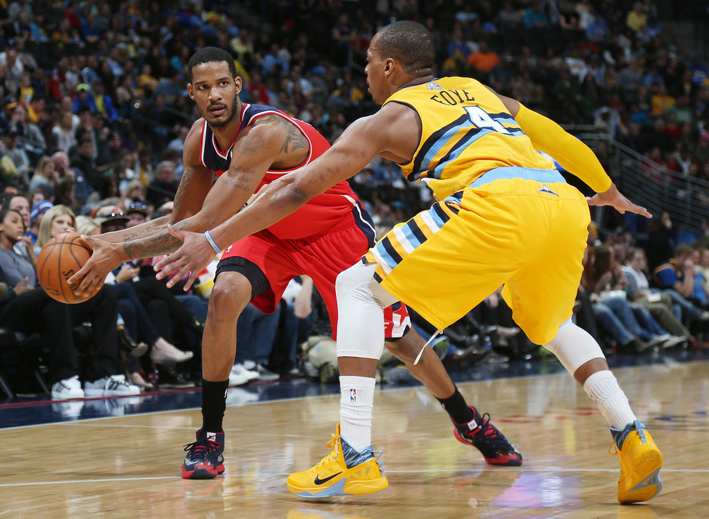 . Washington Wizards forward Trevor Ariza, left, looks to pass ball inside as Denver Nuggets guard Randy Foye covers in the first quarter of an NBA basketball game in Denver on Sunday, March 23, 2014. (AP Photo/David Zalubowski)