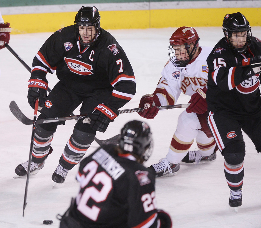 . DENVER, CO. - JANUARY 10: Huskies\' defenseman Kevin Gravel (7) worked the puck past Denver wing Ty Loney (12) in the third period. The St. Cloud State hockey team defeated the University of Denver 6-3 at Magness Arena Friday night, January 10, 2014. Photo By Karl Gehring/The Denver Post