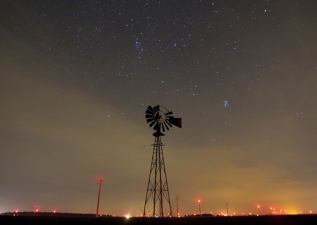 . A meteor streaks through the early morning skies above an old windmill Monday, August 12, 2013, near Brookston, Ind. during the annual Perseid meteor shower  (AP Photo/Journal & Courier, Michael Heinz)