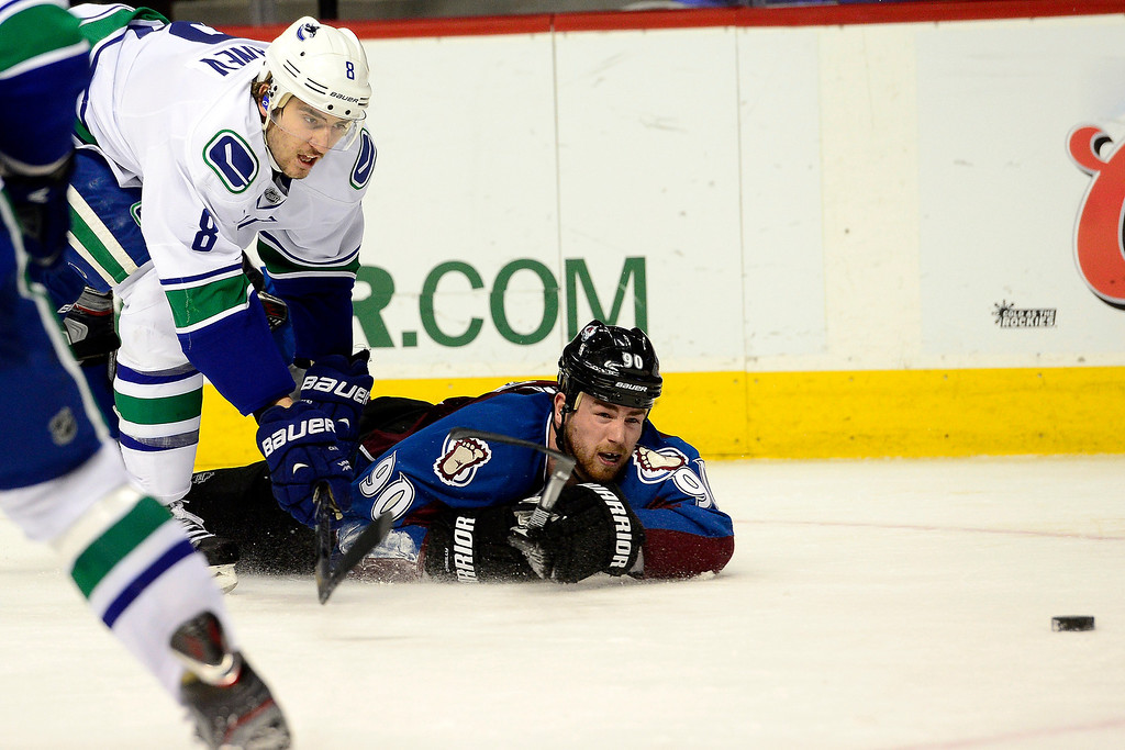 . DENVER, CO - MARCH 24: Chris Tanev (8) of the Vancouver Canucks sends Ryan O\'Reilly (90) of the Colorado Avalanche to the ice during the third period of action. The Colorado Avalanche lost to the Vancouver Canucks 3-2 at the Pepsi Center. (Photo by AAron Ontiveroz/The Denver Post)