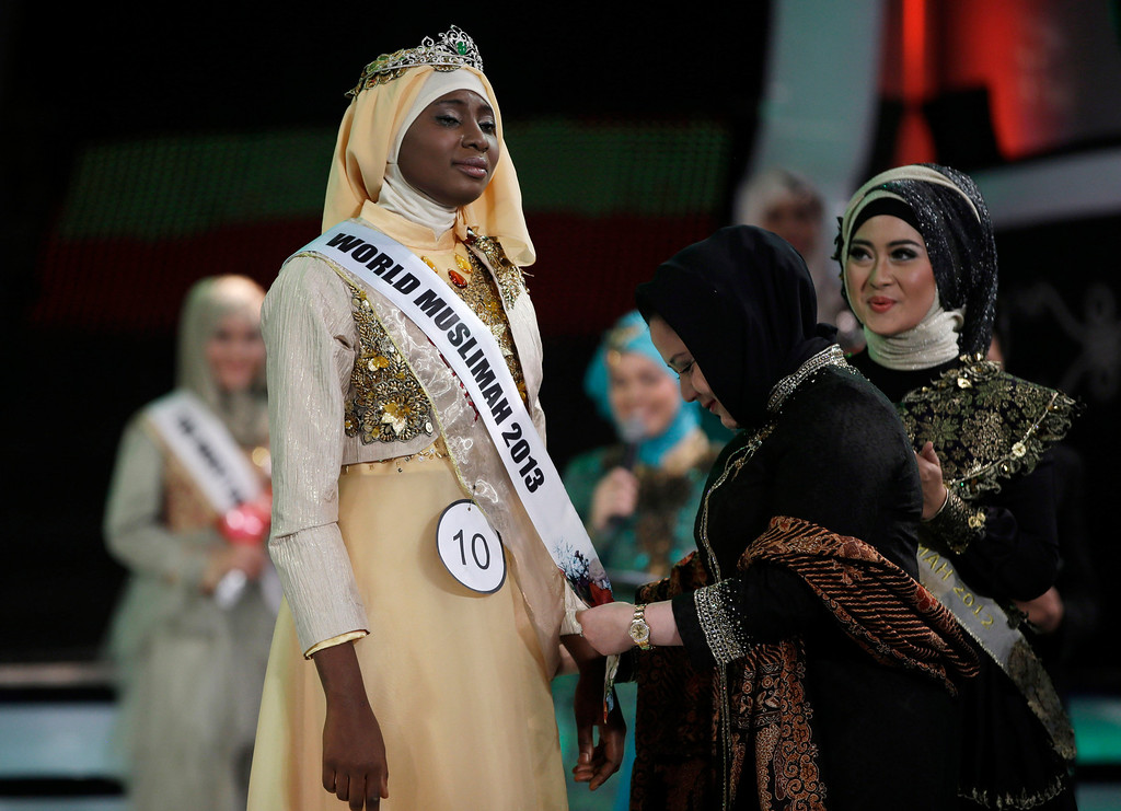 . In this Wednesday, Sept. 18, 2013 photo, Indonesian parliament member Wardatul Asriah, second right, puts a sash on Obabiyi Aishah Ajibola, left, of Nigeria after being named World Muslimah 2013 as World Muslimah 2012 Nina Septiani of Indonesia looks on during the 3rd Annual Award of World Muslimah, a competition billed as the Islamic alternative to Miss World pageant, in Jakarta, Indonesia.  (AP Photo/Dita Alangkara)