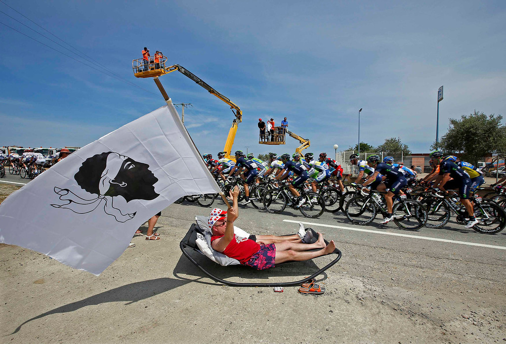 . A fan cheers the pack of riders as it cycles on its way during the 213 km first stage of the centenary Tour de France cycling race from Porto-Vecchio to Bastia, on the French Mediterranean island of Corsica June 29, 2013.  REUTERS/Eric Gaillard