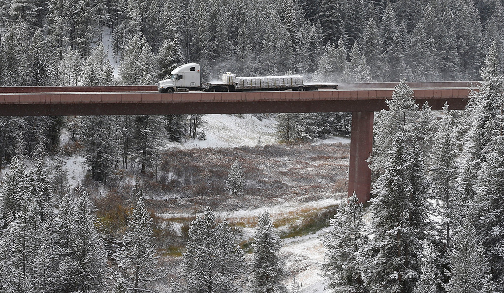 . A truck crosses an elevated section of I-70 after overnight snow fell near Copper Mountain, Colo., Friday Oct. 4, 2013. Powerful storms moved into the Midwest on Friday due to a cold weather system gaining strength as it traveled east from Colorado and Wyoming. (AP Photo/Brennan Linsley)