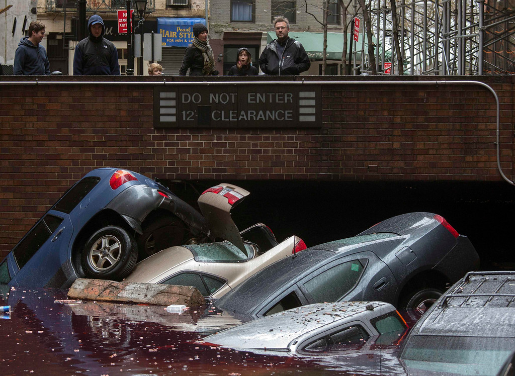 . Residents stand over vehicles which were submerged in a parking structure in the financial district of Lower Manhattan, New York October 30, 2012. Major U.S. stock exchanges expect to open on Wednesday after a monster storm shut down their trading for two days. The southern tip of Manhattan where Wall Street and the NYSE are located lost power on Monday after being buffetted by Sandy, the worst storm to hit New York since at least 1938.  REUTERS/Adrees Latif