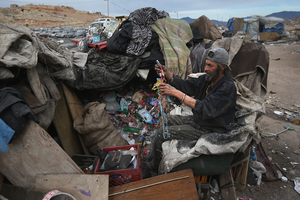 . NOGALES, MEXICO - MARCH 05:  Concepcion Olais sorts through recyclables he found at the Tirabichi landfill on March 5, 2013 in Nogales, Mexico. About 30 families, including Concepcion, live at the dump, searching for recyclables to sell for a living. He and others have received aid from the non-profit Home of Hope and Peace, which plans to expand it\'s assistance to the dump\'s impoverished populace in the future.  (Photo by John Moore/Getty Images)