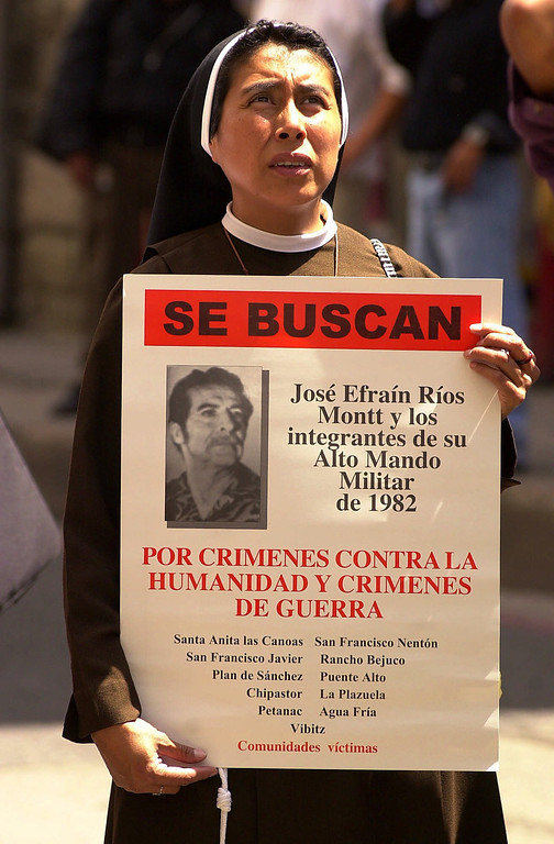 ". A nun carries a poster with a photo of Guatemalan dictator Efrain Rios Montt which reads ""WANTED: Jose Efrain Rios Montt and those associated with his High Military Order of 1982. For war crimes and crimes against humanity\"" in front of the public ministry in Guatemala City, Guatemala, Wednesday, June 6, 2001. Residents of 11 villages hit by army massacres in the early 1980s filed a genocide complaint with prosecutors against former Guatemalan dictator Efrain Rios Montt.  (AP Photo/Jaime Puebla)"