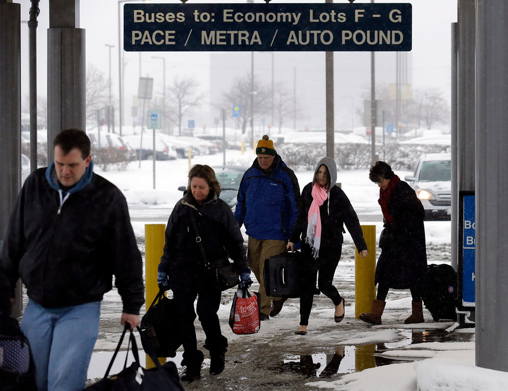 . Travelers walk a train station in the economic parking lot at O\'Hare International Airport in Chicago, Thursday, Jan. 2, 2014. Another one to three inches of snow could fall across the Chicago metro area Thursday with even more falling in the southern part of the region, according to the National Weather Service. (AP Photo/Nam Y. Huh)