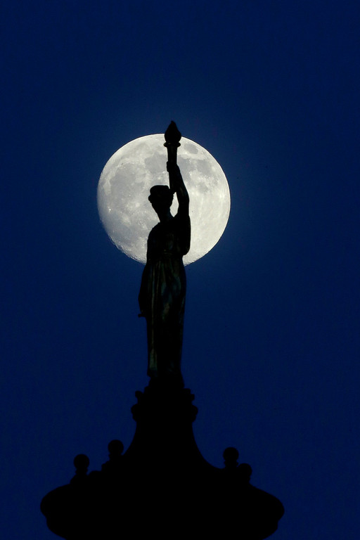 ". The moon in its waxing gibbous stage shines behind a statue entitled ""Enlightenment Giving Power\"" by John Gelert, which sits at the top of the dome of the Bergen County Courthouse in Hackensack, N.J., Friday, June 21, 2013. The moon, which will reach its full stage on Sunday, is expected to be 13.5 percent closer to earth during a phenomenon known as a \""super moon\"".  (AP Photo/Julio Cortez)"