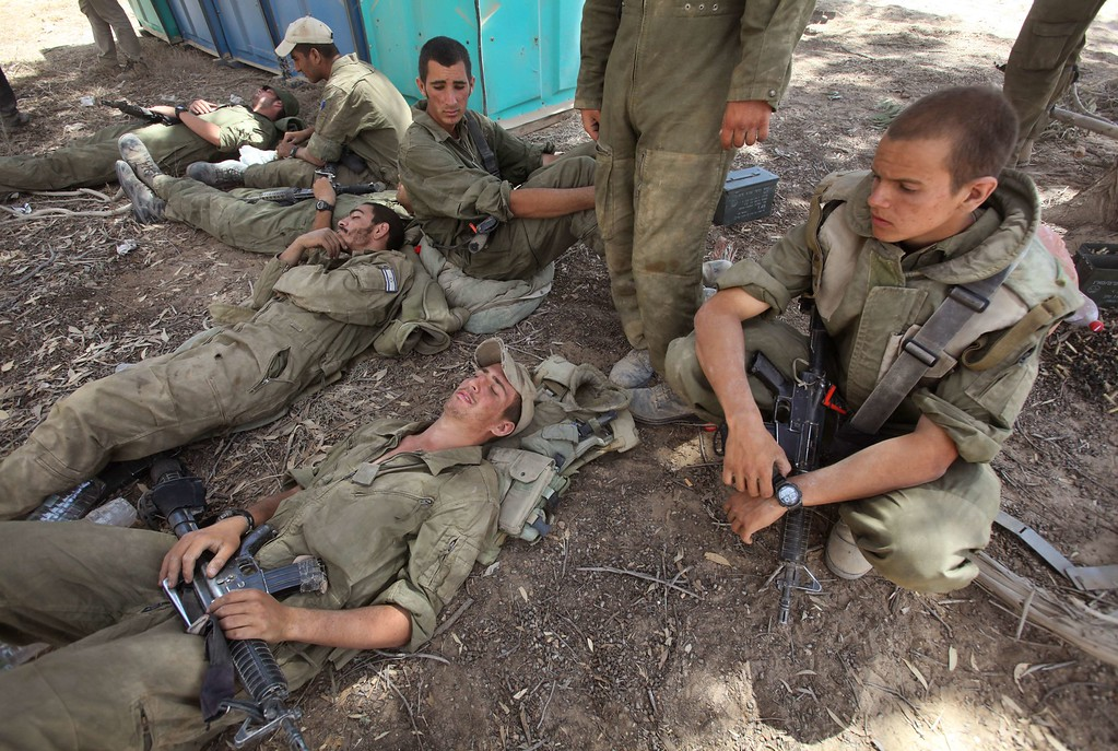 . Israeli soldiers rest along the border between Israel and the Hamas-controlled Gaza Strip after returning from combat in the Gaza Strip on July 31, 2014. Israel said it would not pull troops from Gaza until they finish destroying a network of cross-border tunnels, despite sharp United Nations criticism over the Palestinian civilian death toll. AFP PHOTO/GIL COHEN MAGEN/AFP/Getty Images