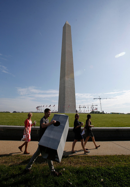 . Steven Avila, an Interior Department employee, carries a Washington Monument costume as he arrives at the Washington Monument in Washington, Monday, May 12, 2014, ahead of a ceremony to celebrate its re-opening. (AP Photo)
