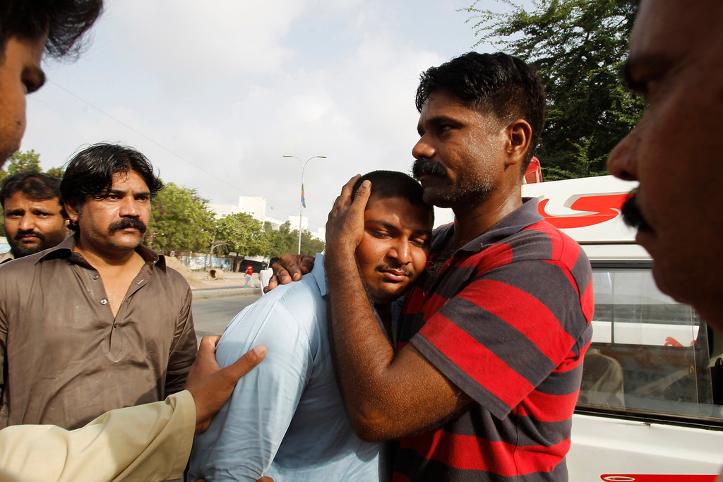 . People comfort a family member of a security officer killed in late Sunday\'s attack at the Jinnah International Airport in Karachi, Pakistan, Monday, June 9, 2014.  (AP Photo/Fareed Khan)