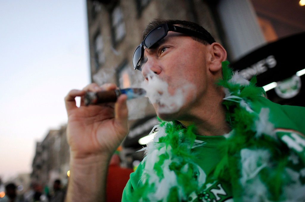 . Shawn Olshefski smokes a cigar along historic River Street while waiting for friends during the 189-year-old St. Patrick\'s Day celebration on River Street, Friday, March 15, 2013, in Savannah, Ga. Savannah, New York and Chicago are all holding parades Saturday to take advantage of the full weekend. (AP Photo/Stephen Morton)