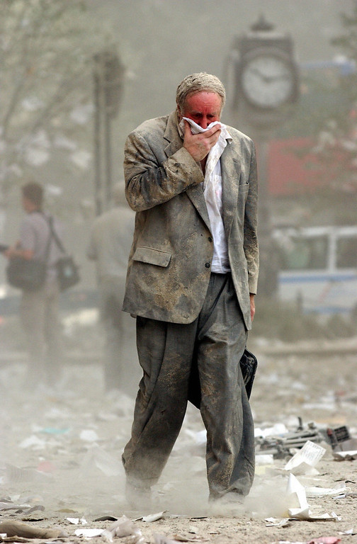 . Edward Fine covering his mouth as he walks through the debris after the collapse of one of the World Trade Center Towers in New York. Fine was on the 78th floor of 1 World Trade Center when it was hit by a hijacked plane 11 September, 2001.        AFP PHOTO/Stan HONDA