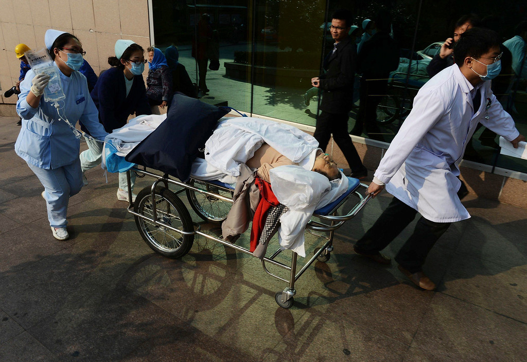 . A doctor and nurses carry an injured person in a stretcher to a hospital following a pipeline explosion in Qingdao in east China\'s Shandong province, Friday, Nov. 22, 2013.  (AP Photo)