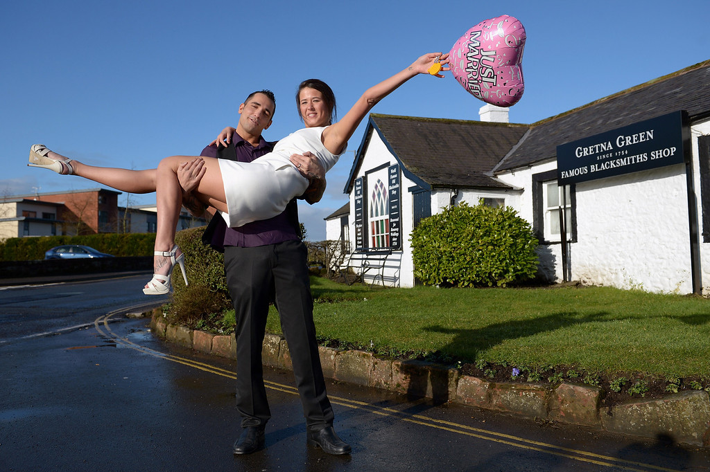 . GRETNA, SCOTLAND - FEBRUARY 14:  Michael Lewis and Rebecca Anderson pose outside the Gretna Green Famous Blacksmiths Shop on the day of their wedding on Valentine\'s day on February 14, 2013 in Gretna, Scotland.   (Photo by Jeff J Mitchell/Getty Images)