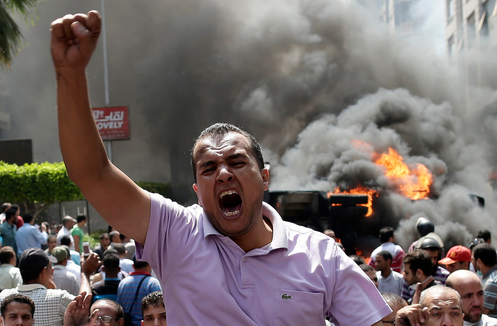 . Supporters of Egypt\'s ousted President Mohammed Morsi chant slogans against Egyptian Defense Minister Gen. Abdel-Fattah el-Sissi during clashes with Egyptian security forces in Cairo\'s Mohandessin neighborhood, Egypt, Wednesday, Aug. 14, 2013.  (AP Photo/Hassan Ammar)