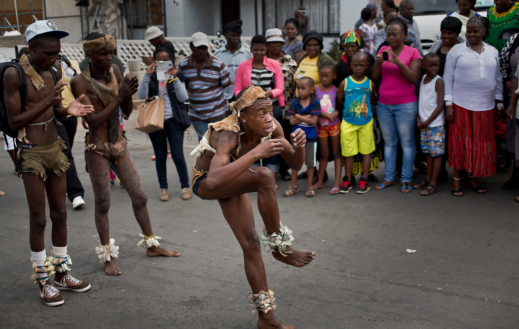 . A troupe of traditional dancers from the Kliptown suburb of Soweto perform outside Nelson Mandela\'s old house in Soweto, Johannesburg, South Africa, Saturday, Dec. 7, 2013. South Africa is readying itself for the arrival of a flood of world leaders for the memorial service and funeral of Nelson Mandela as thousands of mourners continued to flock to sites around the country Saturday to pay homage to the freedom struggle icon. (AP Photo/Ben Curtis)