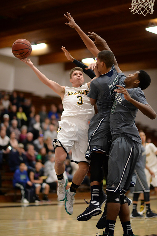 . CENTENNIAL, CO. JANUARY 18: From left, Nick Farmen of Arapahoe High School (3) drives the ball against Ryan Swan (34) and De\'Ron Davis (20) of Overland High School in the 1st half of the game at Arapahoe High School. Centennial Colorado. January 18. 2014. Arapahoe won 62-54.  (Photo by Hyoung Chang/The Denver Post)