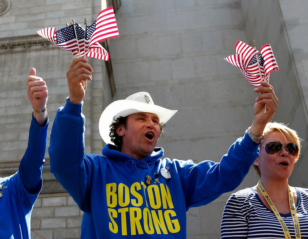 . Boston Marathon bombing hero Carlos Arredondo cheers for runners near the finish line of the 118th Boston Marathon, Monday, April 21, 2014, in Boston. (AP Photo/Elise Amendola)