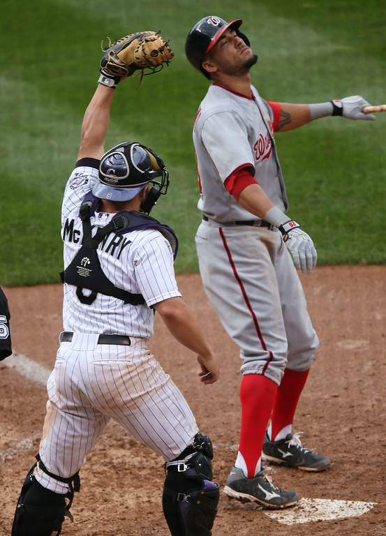 . Washington Nationals\' Ian Desmond, right, reacts after striking out with the bases loaded as Colorado Rockies catcher Michael McKenry holds up the ball in his glove to end the ninth inning of the Rockies\' 6-4 victory in a baseball game in Denver, Wednesday, July 23, 2014. (AP Photo)