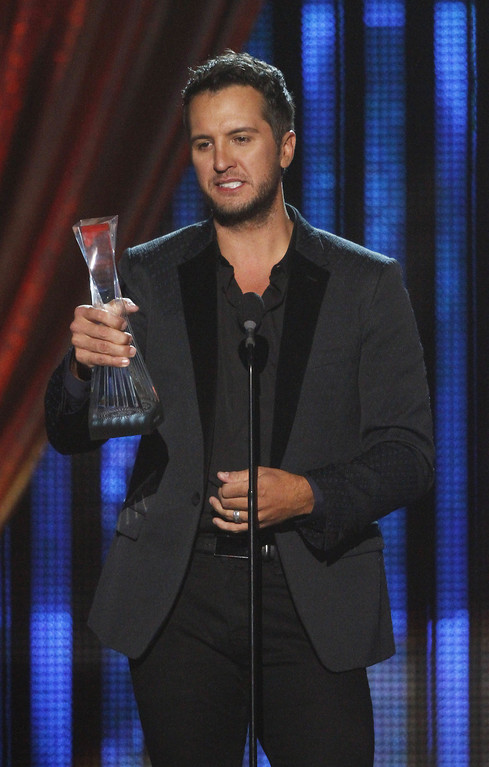 """. Luke Bryan accepts his award at the CMT \""""Artists of the Year\"""" show held at the Music City Center on Tuesday, Dec. 3, 2013, in Nashville, Tenn. (Photo by Wade Payne/Invision/AP)"""