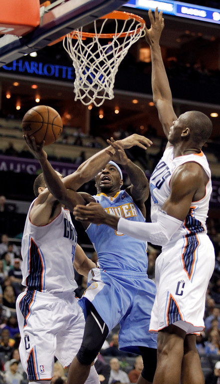. Denver Nuggets\' Ty Lawson (3) splits the defense of Charlotte Bobcats\' Jeffery Taylor, left and Bismack Biyombo to score during the second half of an NBA basketball game in Charlotte, N.C., Saturday, Feb. 23, 2013. The Nuggets won 113-99. (AP Photo/Bob Leverone)