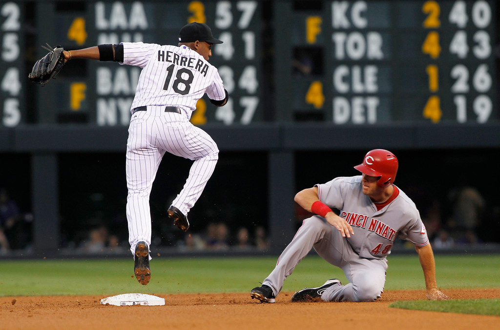 . Colorado Rockies second baseman Jonathan Herrera, left, jumps over Cincinnati Reds\' Ryan Ludwick after forcing him out at second base on the front end of a double play hit into by Todd Frazier to end the top of the first inning of a baseball game in Denver on Saturday, Aug. 31, 2013. (AP Photo/David Zalubowski)