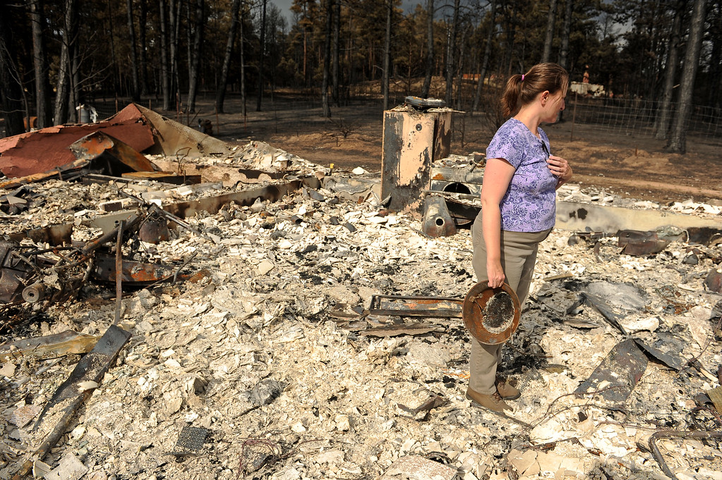 . Amy Feik holds an old helmet from World War I that she found in the rubble of what was the home she shared with boyfriend Robert Runyard in Black Forest, Co on June 18, 2013.  feik and Robert Runyard, not pictured, returned home for the first time to their home on Swan Road in Black Forest, CO on June 17, 2013.  Residents of Black Forest were finally allowed back into their burned homes for the first time since the fire devoured thousands of acres inside the Black Forest taking with it 502 homes and two lives.  Photo by Helen H. Richardson/The Denver Post)